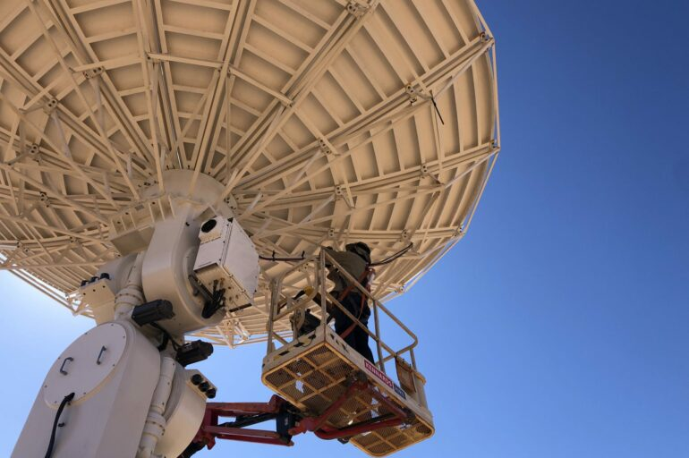 CfAT technicians put the finishing touches on the satellite dish for the earth ground station in Alice Springs. Image: Ekistica Ltd.