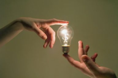 A glowing incandescent lightbulb held between the index fingers of two hands.