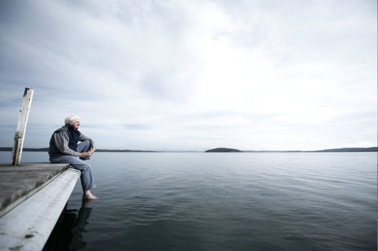 Elderly man sitting on the end of pier looking over expanse of open water.