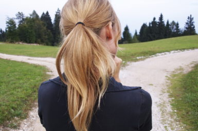 The back of a female head. She is trying to decide which of two paths to follow.