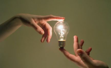Lightbulb held between the index fingers of two hands