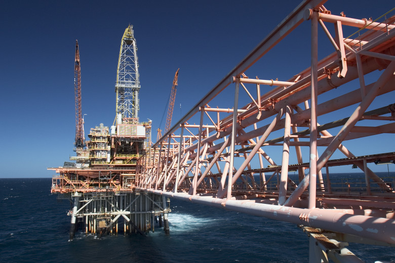Looking along a boom of an oil rig out at sea