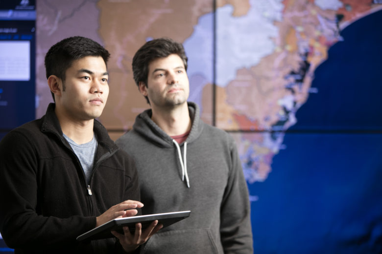 Two young men, one with a tablet, standing in front of a map displayed on multiple screens.