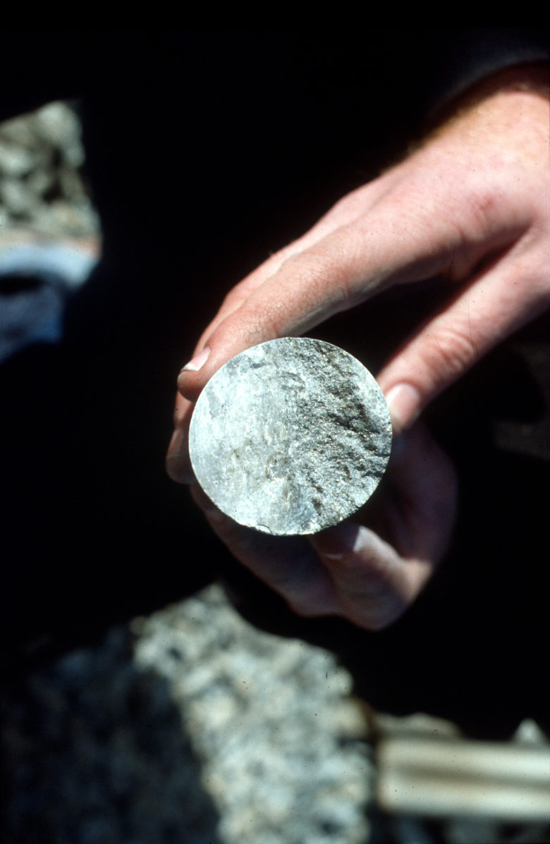 Mine core sample cross section held in a hand