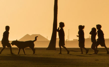 Children playing on the foreshore of an industrial port in the sunset.
