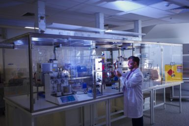 A researcher in a lab coat stands in front of machines in a glass cabinet