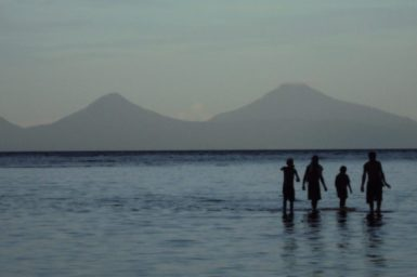 Family standing in the sea across from mountains