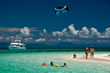 A tropical island beach with swimmers. a boat and a parasail
