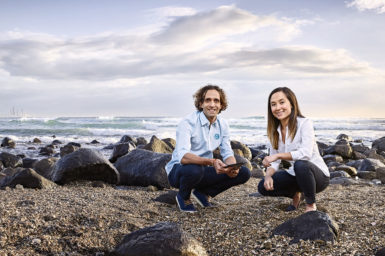 A man and woman squat on a rocky beach
