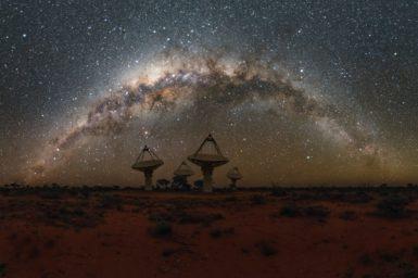 Radio telescope antennas in the desert beneath the Milky Way